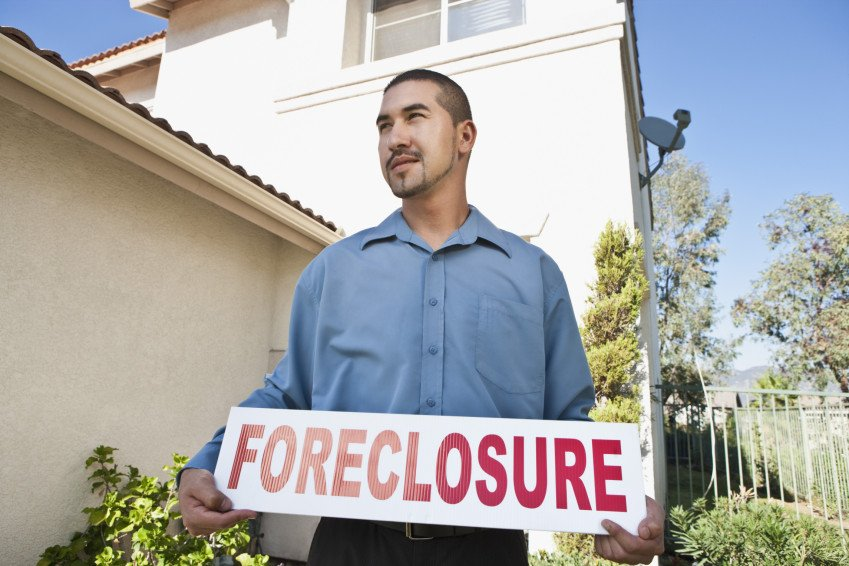 """Man Holding Sign Outside House"", via moodboard, ThinkStock."