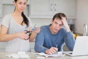 """""""Disappointed Couple in the Kitchen Cutting Up Credit Card"""", via Wavebreakmedia LTD, ThinkStock."""