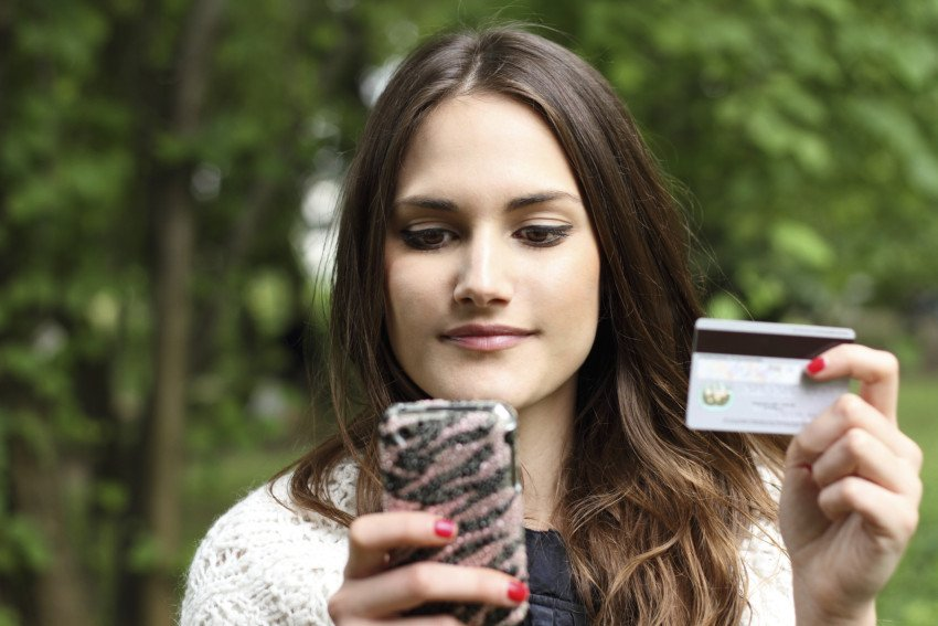 """""""Beautiful Woman with Mobile Phone and Credit Card"""", via orlando123, ThinkStock."""
