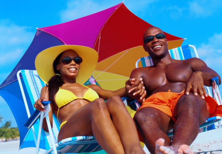 """Couple Wearing Swimsuits Holding Hands Sitting on a Beach"", via Stockbyte, ThinkStock."