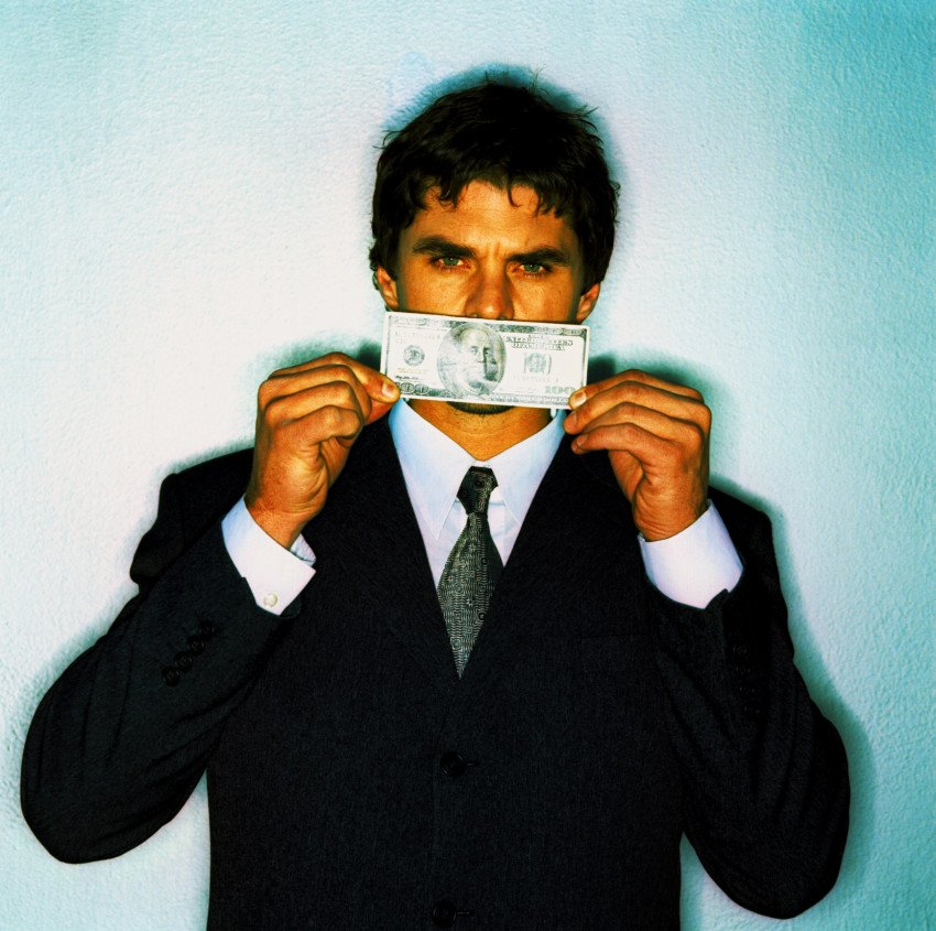 """A Businessman Covering His Mouth With a Currency Note"", via George Doyle, ThinkStock."