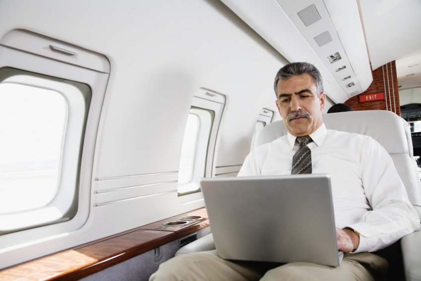 """Businessman Working on Laptop on Private Plane"", via Fuse, ThinkStock."