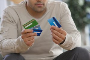 """Man choosing credit cards"" via Huntstock on Thinkstock"