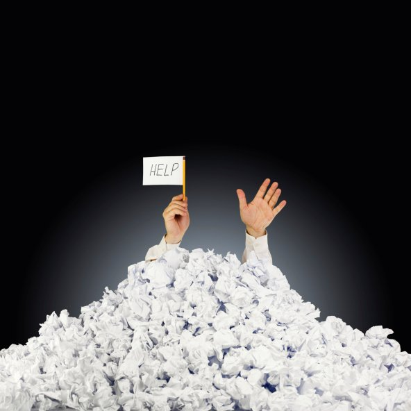 Person under crumpled pile of papers with help sign